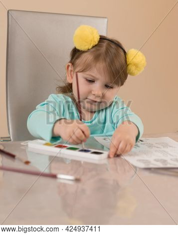 A Little Girl In A Funny Headband With Yellow Pompoms Paints With A Brush On A Chair At The Table