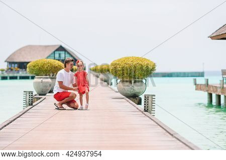 Little Girl With Dad On Wooden Jetty Near Water Bungalow At Exotic Resort