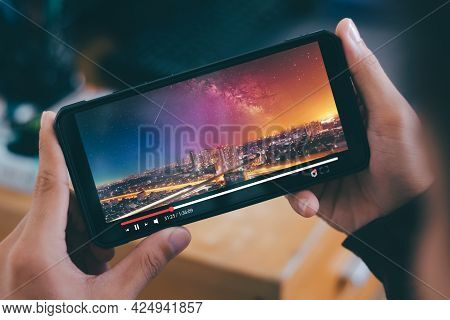 Online Movie Stream With Smartphone. Young Man  Watching Film On Mobile Phone With Imaginary Video P