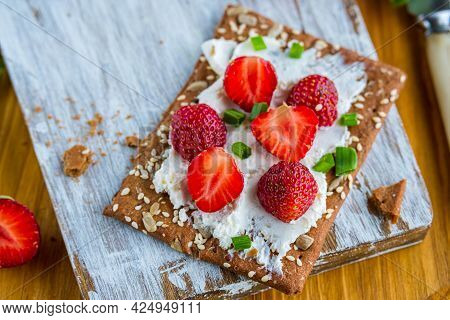 Snack Or Breakfast, Rye Crispbread With Cream Cheese, Green Onions And Fresh Strawberries On A Woode
