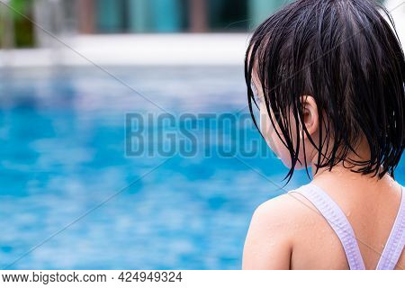 Rear View Child Girl Wearing Swimming Suit In Blue Pool. Kid Playing Water In The Summer Time. Child
