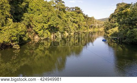 A Calm Country Creek With The Trees On The Banks Reflected In The Water And A Pumping Station On The