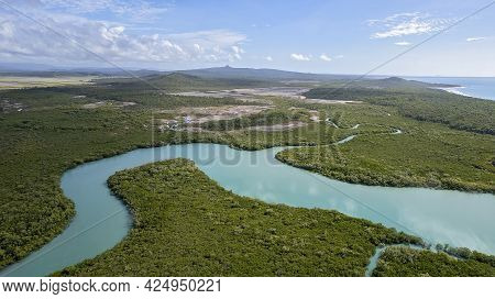 Aerial Over A Blue Water Creek Flowing From The Ocean And Winding Amongst A Mangrove Bushland Enviro