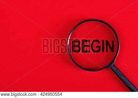 Magnifier With The Word - Begin, On A Red Background.