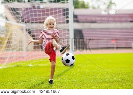 Kids Play Football On Outdoor Stadium Field. Children Score A Goal During Soccer Game. Little Boy Ki