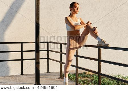 Beautiful Female With Dark Hair And Ponytail Sitting On Railing, Wearing White Top And Beige Leggins