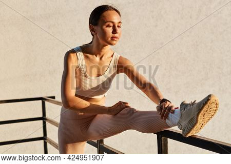 Portrait Of Winsome Woman With Ponytail Wearing White Top And Beige Leggins, Stretching Leg, Doing S