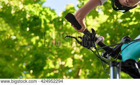 A Teenager Girl In A Bicycle Helmet Rides A Bicycle In The Park. Bottom View With Focus On The Bicyc