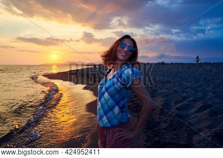 Woman on beach in sunset. People in vacation. Beautiful woman on beach in vacation in sunset. People in vacation. Happy people. Happy beautiful woman in vacation in sunset. Woman silhouette in sunset in vacation. Woman. People. Sunset. Vacation.