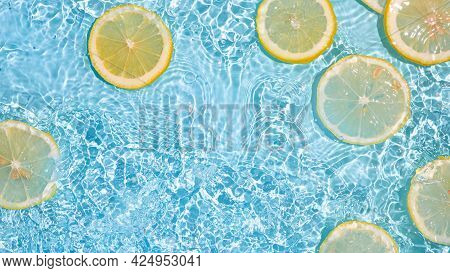 Lemon Slices In Clean Transparent Water Over Blue Background With Copy Space. Water Splashing On Blu