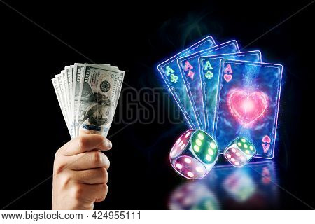 Concept For Online Casino, Gambling, Online Money Games, Bets. A Man's Hand Holds Dollars On A Backg