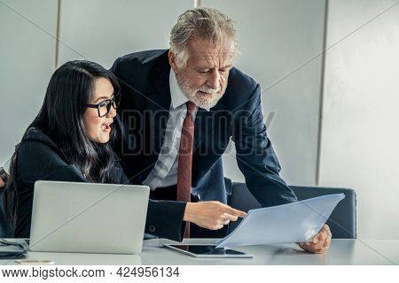 Senior Executive Manager And Young Businesswoman Working In Meeting Room In The Office. The Woman Is