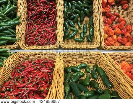 Fresh Chillies Variety Piled In The Baskets On The Market. Green Cayenne, Red Chilli, Habanero Chill