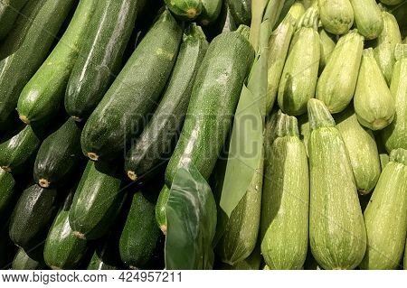 Fresh Piled Green Zucchini And Grey Zucchini, Gray Squash On The Market. Food Background. Harvest. H