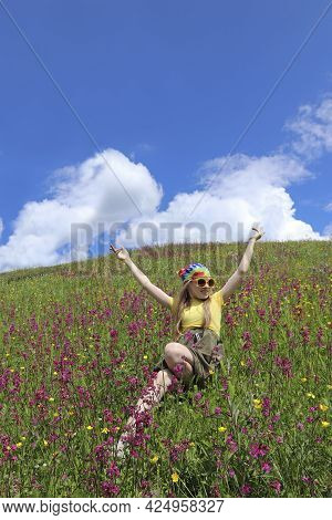 The Girl Is In A Good Mood In A Field Among Flowers.