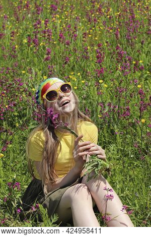 Portrait Of A Girl With A Smile In A Field With Flowers In Summer.