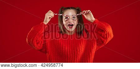 Pretty girl holding colourful sweet christmas candy sticks in a heart form. Happy smiling teenager with makeup over red background.