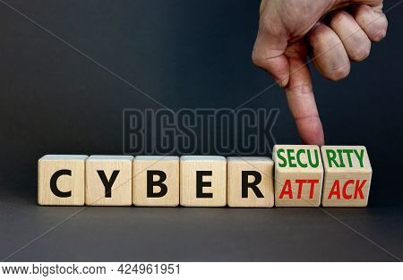 Cyber-security Vs Cyber-attack Symbol. Businessman Turns Wooden Cubes, Changes Words Cyber-attack To