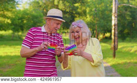 Senior Stylish Couple Grandmother Grandfather Squeezing Presses Colorful Anti-stress Push Pop It Pop