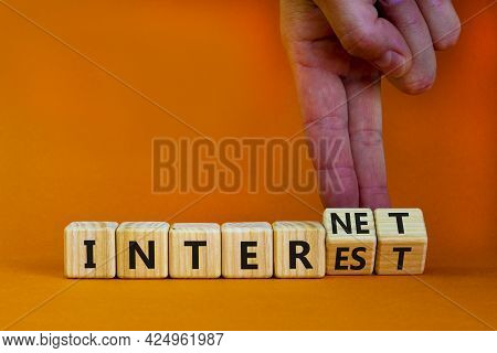 Internet And Interest Symbol. Businessman Turns Wooden Cubes And Changes The Words Interest To Inter