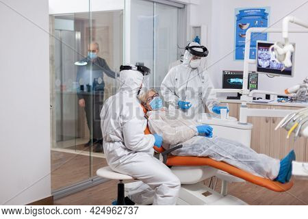 Senior Patient Wearing Hazmat Suit During Coronavirus In Dentist Office Elderly Woman In Protective