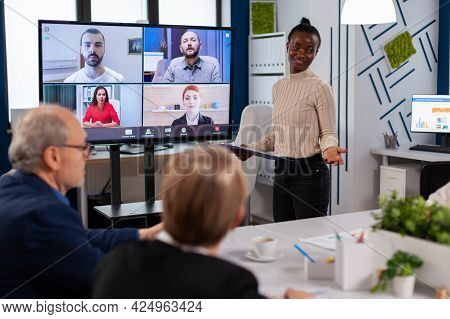 Black Manager Woman Talking With Remotely Colleagues On Video Call At Tv Screen, Presenting New Busi