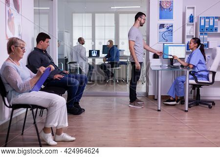Crowded Hospital Waiting Area With People Filling Form For Medical Consultation, Young Man Giving Xr
