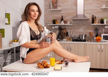 Dreamy Lady With Tattoos In Provocative Underwear Sitting On Kitchen Table. Provocative Young Woman