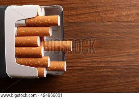 Pack Of Cigarettes On Wooden Table, Above View. Space For Text
