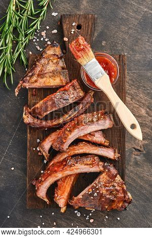 Grilled And Smoked Pork Ribs With Barbeque Sauce On An Old Vintage Wooden Cutting Board. Tasty Snack