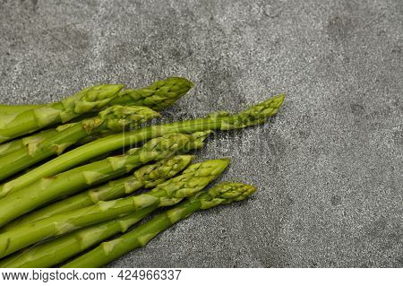 Close Up Bunch Of Fresh Green Asparagus On Cutting Board Or Grey Stone Table Surface, High Angle Vie