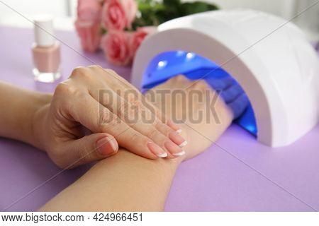 Woman Using Ultraviolet Lamp To Dry Gel Nail Polish At Violet Table, Closeup