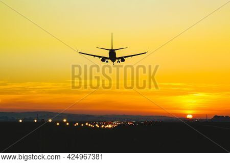 Airplane Landing On The Runway During Sunset And Dusk
