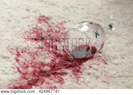 Overturned Glass And Spilled Red Wine On White Carpet