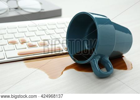 Cup Of Coffee Spilled Over Computer Keyboard On White Wooden Table