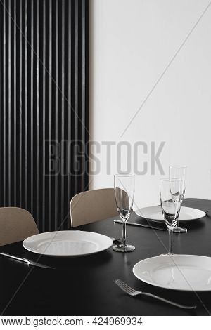 Vertical Shot Of Black Matt Table With Dinnerware, Wineglasses And Serving Cutlery In Minimalist Mod