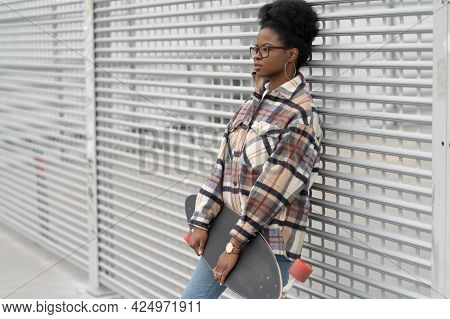 Street Fashion: African American Woman, Young Skater Dressed In Trendy Casual Clothes With Longboard
