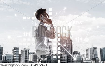 Double Exposure Of Elegant Businessman Standing Facing The City And Talking His Mobile Phone
