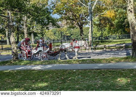 New York, Usa - Oct 21, 2015: People Enjoy Carriage Ride In Central Park  In Manhattan. Horse-drawn