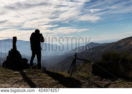 Man In Backlight Photographing Mountains And Blue Sky With Clouds