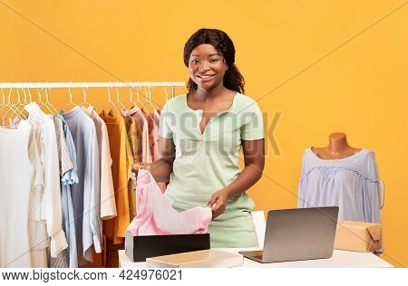 Young Black Lady Packing Clothes Into Parcel, Standing At Table With Laptop Near Clothing Rack On Or