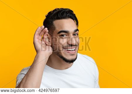 Closeup Portrait Of Cheerful Arab Guy Eavesdropping And Smiling