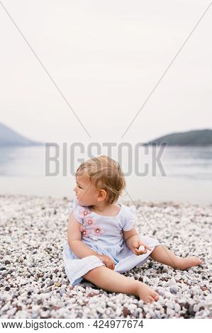 Little Girl In A Dress Sits On A Pebble Beach, Turning Her Head Back