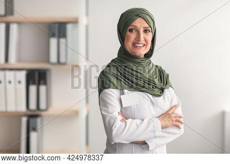 Mature Muslim Doctor Woman Wearing Hijab Posing In Clinic Office