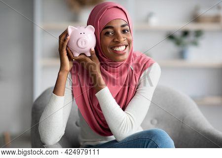 Saving Money. Positive Black Islamic Lady In Headscarf Holding Piggybank