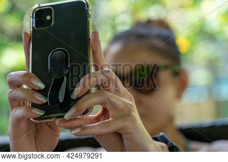Female Hand While Holding A Cellphone Doing Selfie. Blurry Face Focused On Hand And Cellphone
