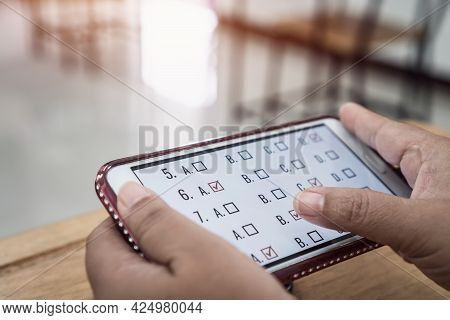 Student Testing E-learning Exam On Technology Smartphone Clicking Multiple Choice Questions. Educati