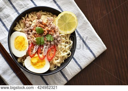 Instant Noodles With Minced Pork, Boiled Egg, Lemon Grass, Chilli And Lemon In A Black Bowl With Cop