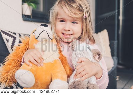 Little Girl Smiling And Hugging Two Plush Toys Dog And Cat.