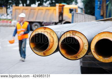 Metal Pipes With Thermal Insulation Against The Background Of A Builder In A Helmet And A Special Or